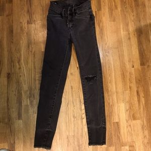 Black distressed jeans, with a whole in the knee.